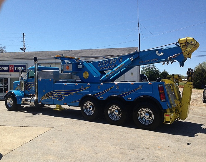 Blue tripple axle Alvey's Towing Truck in front of the shop